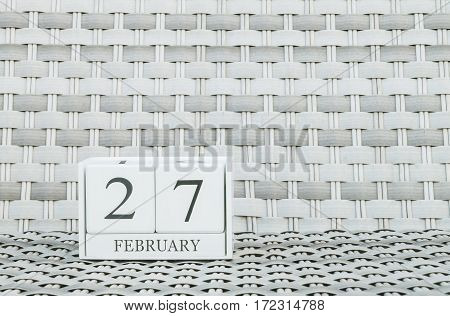 Closeup surface white wooden calendar with black 27 february word on blurred weave wood chair textured background with copy space in selective focus at the calendar