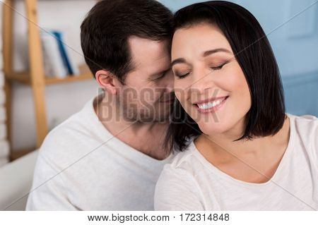 Being in love. Delighted joyful pleasant couple sitting together and smiling while being in love with each other