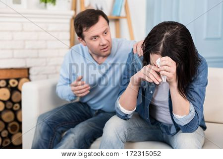 Overwhelmed by emotions. Sad cheerless young woman holding her head down and hiding her face while crying