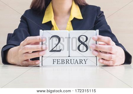 Closeup white wooden calendar with black 28 february word in blurred working woman hand on wood desk in office room in selective focus at the calendar