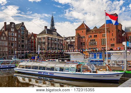 AMSTERDAM, NETHERLANDS - JULY 07, 2015: Cruise boat and Old City of Amsterdam - capital of Netherlands, one of the most popular tourist destinations with more than 5 million visitors annually.