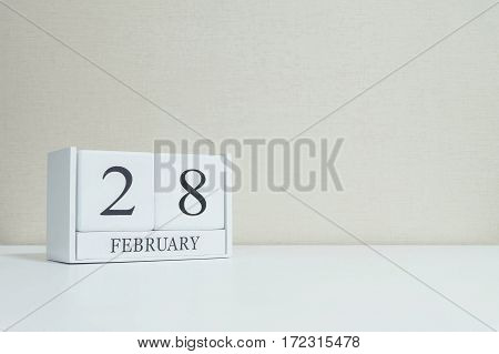 Closeup white wooden calendar with black 28 february word on blurred white wood desk and cream color wallpaper in room textured background with copy space in selective focus at the calendar