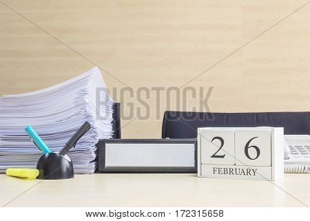 Closeup white wooden calendar with black 26 february word on blurred brown wood desk and wood wall textured background in office room view with copy space in selective focus at the calendar