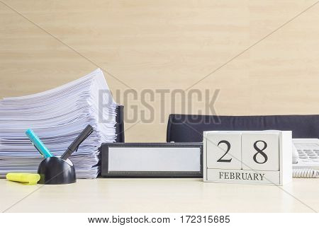 Closeup white wooden calendar with black 28 february word on blurred brown wood desk and wood wall textured background in office room view with copy space in selective focus at the calendar