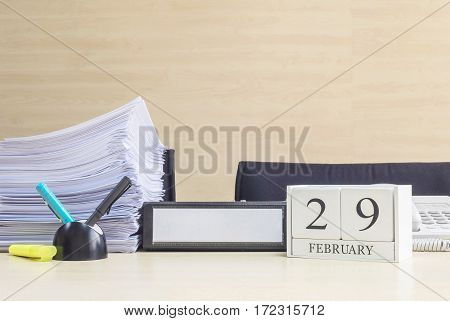 Closeup white wooden calendar with black 29 february word on blurred brown wood desk and wood wall textured background in office room view with copy space in selective focus at the calendar