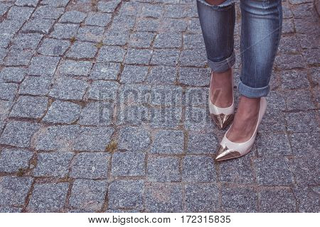 Female Legs In A Beautiful Peach High-heeled Shoes With Gold Nose. Close-up. On The Granite Pavement