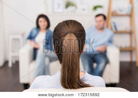 Couple and family psychology. Professional nice female psychologist sitting opposite her patients and looking at them while having a psychological session