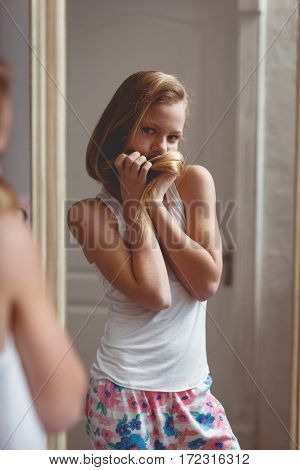 Teenage girl checking her face and body in the mirror