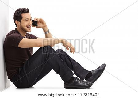 Young man talking on a phone while sitting on the floor and leaning against a wall isolated on white background