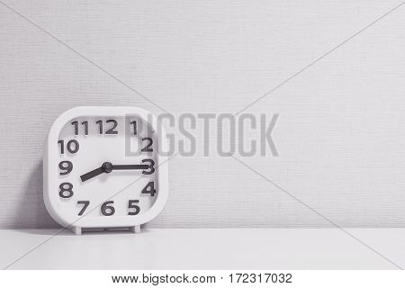 Closeup white clock for decorate show a quarter past eight or 8:15 a.m. on white wood desk and cream wallpaper textured background in black and white tone with copy space