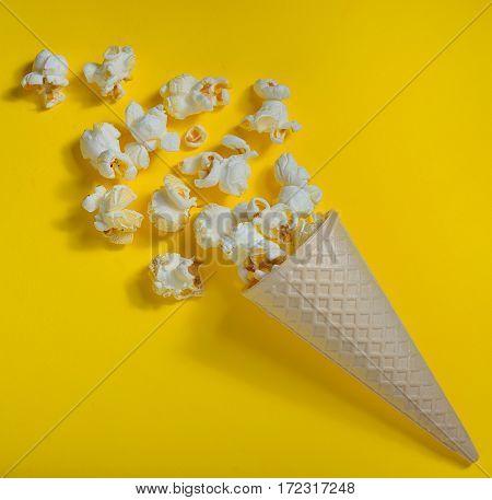 Popcorn in ice cream cones on yellow background