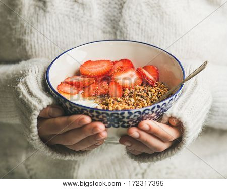 Healthy breakfast greek yogurt, granola and strawberry bowl in hands of woman wearing white loose woolen sweater, selective focus. Clean eating, healthy, vegetarian, dieting food concept