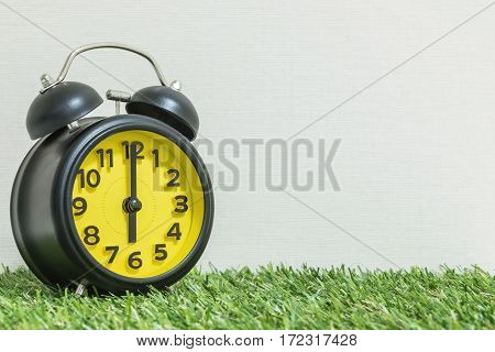 Closeup black and yellow clock for decorate in 6 o'clock on green artificial grass floor and cream wallpaper textured background with copy space