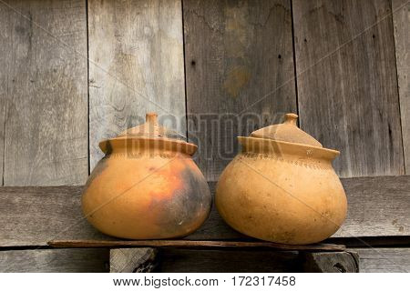 Couple of clay pots different style, used and new, with wooden background.