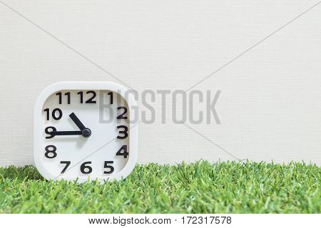 Closeup white clock for decorate show a quarter to eleven or 10:45 a.m. on green artificial grass floor and cream wallpaper textured background with copy space