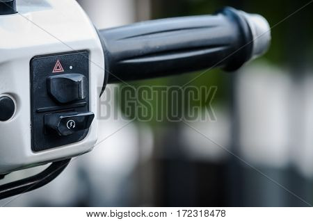 Close up handlebars of motorcycle on green nature background.
