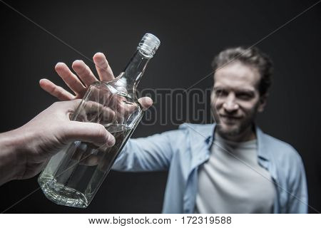 Your choice. Smiling man wearing casual clothes striving after bottle while standing isolated on grey background