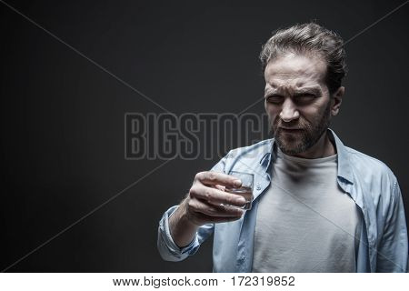 Heavy drinker. Dissatisfied man wearing blue shirt over white T-shirt keeping small glass in right hand while looking angrily aside