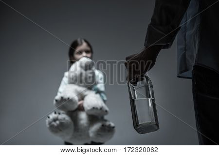 Family problems. Little scared girl looking straight at father while hugging big toy standing over grey background