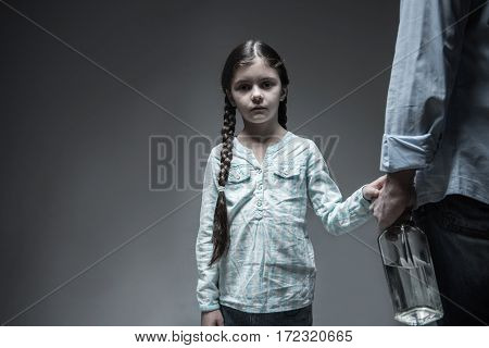 I want changes. Serious girl with two braids wearing casual clothes putting her hand on her fathers hand, who holding big bottle with alcohol