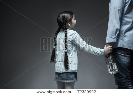 Think about future. Sad daughter wearing jeans skirt and striped shirt having two long braids putting her hand on the hand of her father, isolated on grey