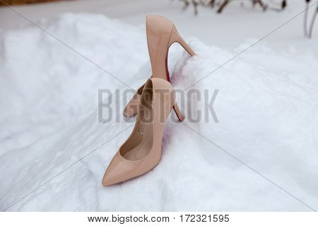 Pair of beige women heels shoes on snow. Winter scene. Fashion and wedding ideas. Christmas background.