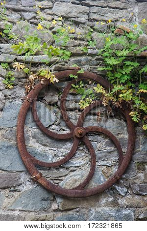 Garden decoration with old and weathered wooden cart wheel