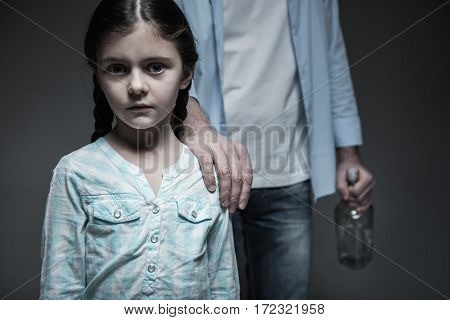 Obedient child. Poor little female wearing jeans skirt and striped shirt standing in front of her dad, who keeping his hand on her shoulder posing over grey background