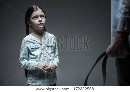 Think what you are doing. Astonished little girl pressing lips holding her hands together while looking at father with belt in hand