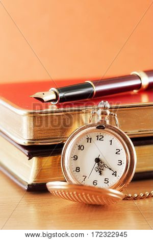 Beautiful pen and pocket watch on the notebook