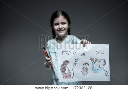 It is my life. Attractive girl from unhappy family holding colorful pencils in right hand and picture in left hand while looking straight at camera