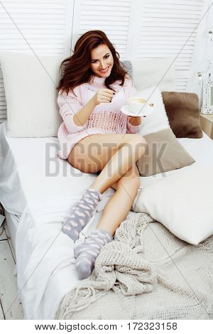 young pretty brunette girl laying in cozy bed with coffee wearing wool winter sweater happy smiling, lifestyle people concept close up