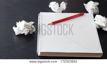 Red pencil and notebook on a black table
