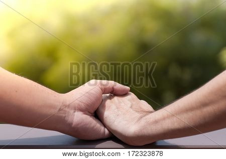 Close up of men gay couple holding hands on green natural background. Valentines. Wedding.