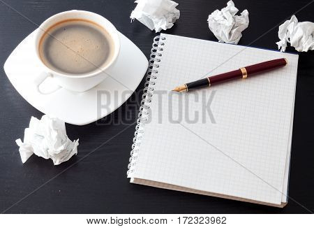 Coffee pen and notebook on a black table