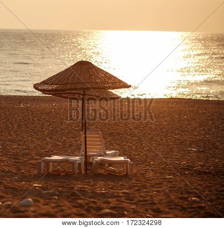 Dreamy beach with sun loungers under parasol on the setting sun
