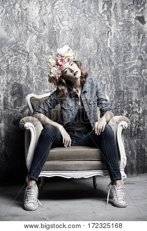Modern young woman wearing casual jeans clothes and wreath of flowers posing in vintage armchair. Cosmetics and make-up. Spring and summer fashion.