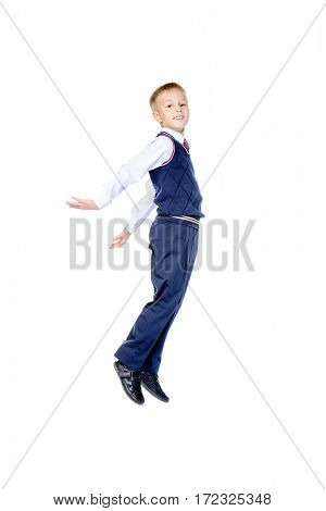 Happy schoolboy jumping for joy. Isolated over white background. Happiness, activity and child concept. School uniform. Copy space.