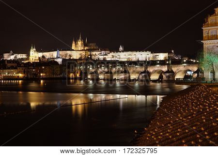 Famous Unesco panorama of Hradcany in the Czech Republic with enlightened Charles Bridge reflected in Vltava river and Prague Castle in the background