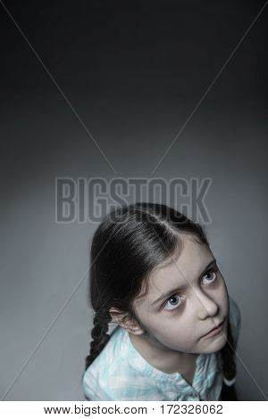 Follow me. Frightened girl standing over grey background wearing blue shirt pressing her lips