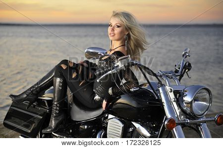 Young beautiful woman posing on a bike
