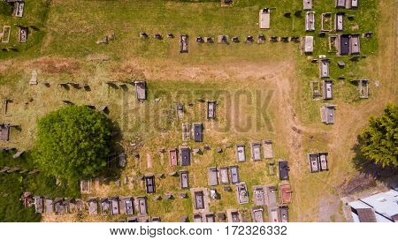 Aerial downward view of a graveyard. A well used path in the grass is visible