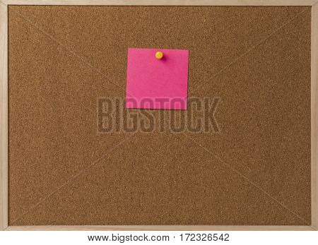 Pink Blank sticky notes yellow pinned into brown corkboard