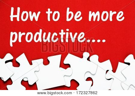 The words How to be More Productive in white text on a red background above blank white jigsaw puzzle pieces