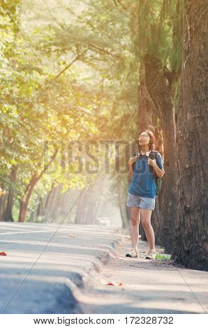 Asian woman hiker with backpack standing and breathing fresh nature air. Happiness of girl and smiling on vacation.