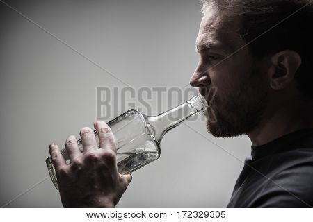 Need one more. Thoughtful male person wearing grey T-shirt drinking alcohol beverage standing in semi position
