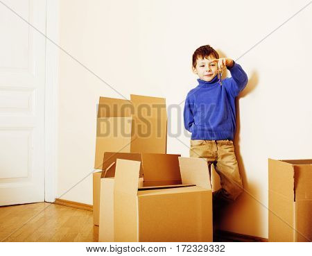 little cute boy in empty room, remoove to new house. home alone emong empty boxes close up kid smiling