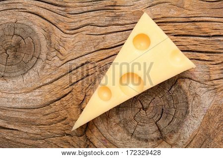 Emmental cheese isolated on wooden background in studio