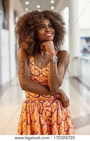 Portrait of attractive afro-american woman with curly hair and in beautiful dress