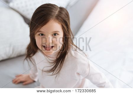 Naughty child. Happy cute pretty girl looking at you and showing her tongue while looking at you